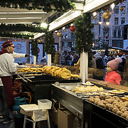 "BUDAPEST, HUNGARY - DECEMBER 07:  Customer buy ""Langos"" (Deep Fried Dough) an Hungarian speciality at the  Vorosmarty Square Christmas market on December 7, 2017 in Budapest, Hungary. The traditional Christmas market and lights will stay until 31st December 2017."