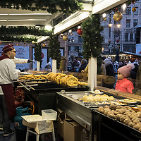 """BUDAPEST, HUNGARY - DECEMBER 07:  Customer buy """"Langos"""" (Deep Fried Dough) an Hungarian speciality at the  Vorosmarty Square Christmas market on December 7, 2017 in Budapest, Hungary. The traditional Christmas market and lights will stay until 31st December 2017."""