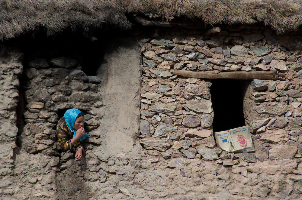 The highest mountain range in North Africa, the High Atlas runs diagonally across Morocco.  The Toubkal region contains the highest peaks.  It is only two hours from Marrakesh.  Here, a girl peers from a window in a traditionally built home high in the Atlas mountains of Morocco.