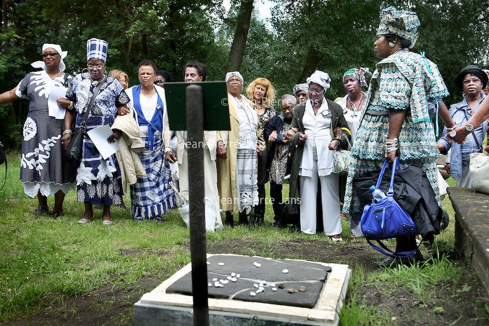 Nederland, Ouderkerk ad Amstel , 29 juni 2011..Herdenking bij het graf van de zwarte Joodse slaaf Elieser die in 1629 werd begraven op de Joodse Begraafplaats in Ouderkerk ad Amstel..Aan het woord is 1 van de sprekers mevrouw Nana Abrewa. (Vooraan rechts).Mevrouw Helouise Held (1948), meer bekend als Nana Abrewa, is geen onbekende in de Amsterdamse samenleving. Als kenner van de Afro-Surinaamse cultuur, geboren in Paramaribo en sinds 1972 woonachtig in Nederland, is zij actief in veel culturele organisaties. Momenteel is Nana Abrewa voorzitter van de vereniging Kopro Beki Prodo, die jaarlijks de Bigi Spikri optocht op 1 juli aanvoert. In 2007 is zij door radio RAZO verkozen tot vrouw van het jaar vanwege haar sociale betrokkenheid..Commemoration at the grave of black Jewish slave Elieser , buried in 1629 at the Jewish Cemetery at Ouderkerk ad Amstel.