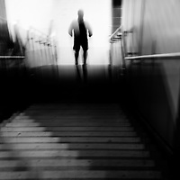 A blurred man at the bottom of a set of stairs in strange light.