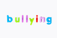 Colorful alphabet magnets spell 'bullying' over white background