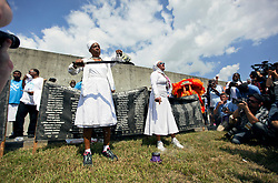 29 August 2015. Lower 9th Ward, New Orleans, Louisiana.<br /> Hurricane Katrina 10th anniversary.<br /> Mourners gather to remember those who perished during the storm. The ceremony is conducted close to where a barge broke through the levee a decade earlier causing widespread flooding and loss of life. <br /> Photo credit©; Charlie Varley/varleypix.com.