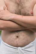 close up of the belly of an adult man with folded arms