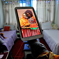Eritrean woman showing a photograph of herself and her roommate in their best costume, in the room they share at a centre run by the Hospice Generale for refugees and asylum seekers.