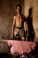 Portrait of a man removing excess from leather in Fez Tannery Quarter.