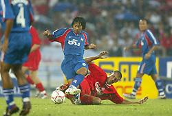 BANGKOK, THAILAND - Thailand. Thursday, July 24, 2003: Liverpool's Bruno Cheyrou tackles Thailand's Issawa Siriwong during a preseason friendly match at the Rajamangala National Stadium. (Pic by David Rawcliffe/Propaganda)