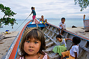 Kids playing in a long-tail boat at the beach in front of the Chao Leh (Sea Gipsy)village.