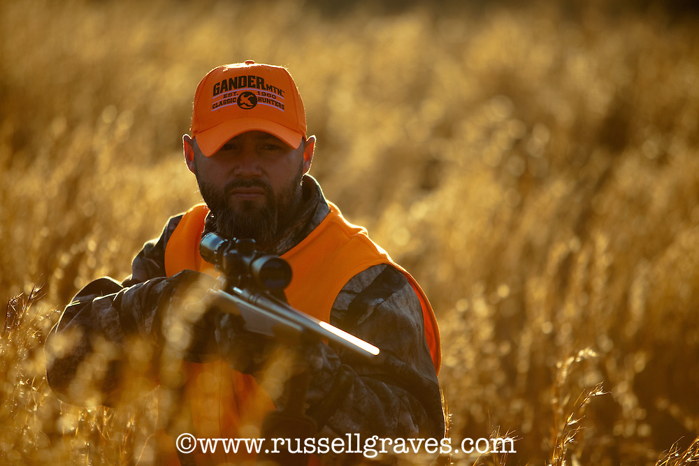 BACKLIT DEER HUNTER WEARING BLAZE ORANGE IN A GRASS MEADOW