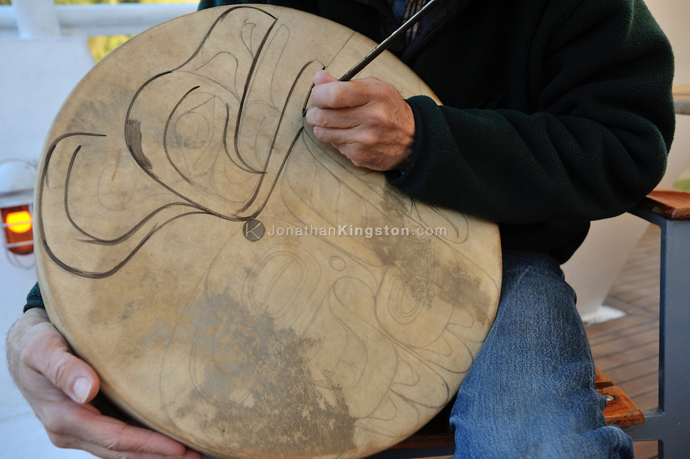 A artist paints a traditional pacific northwest Native American design on the face of a hand drum.