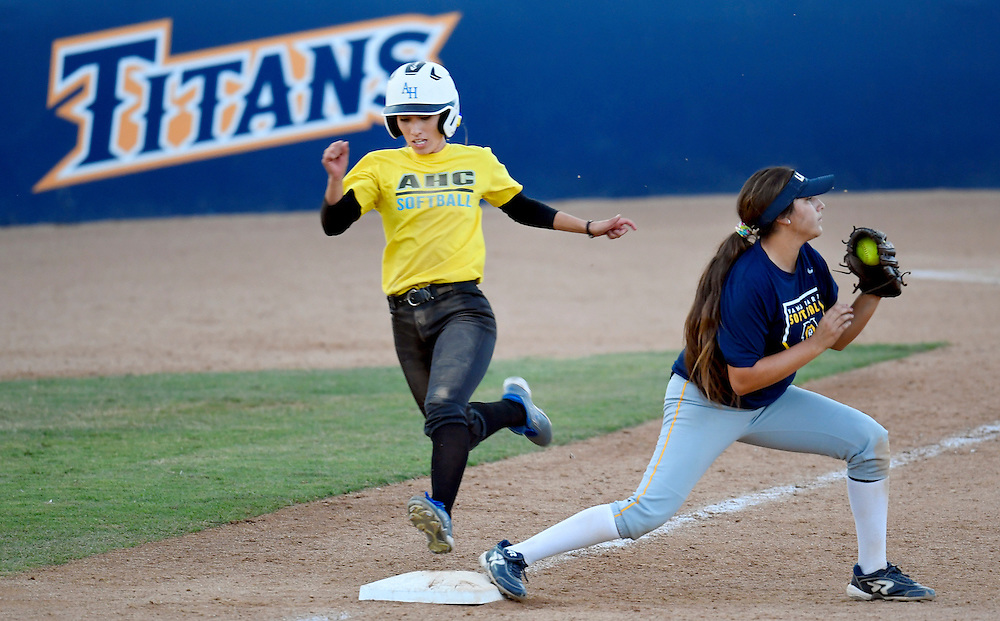 A player gets out at first base after hitting the ball during the fall ball softball game at Cal State Fullerton in California on Friday.