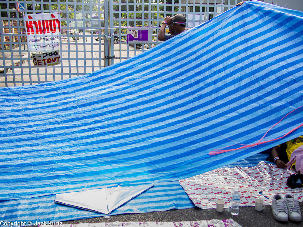 "24 DECEMBER 2013 - BANGKOK, THAILAND:  Protestors string up a tarp in front of one of the chained gates to the Thai-Japan Stadium in Bangkok. The sign on the gate says ""E-Poo get out,"" E-Poo is a nickname for caretaker Prime Minister Yingluck Shinawatra. Hundreds of anti-government protestors are camped out around the Thai-Japan Stadium in Bangkok, where political parties are supposed to register for the election on February 2. As of Dec 24, nine of the more than 30 parties were able to register. Protestors hope to prevent the election. The action is a part of the ongoing protests in Bangkok that have caused the dissolution of the elected government.     PHOTO BY JACK KURTZ"
