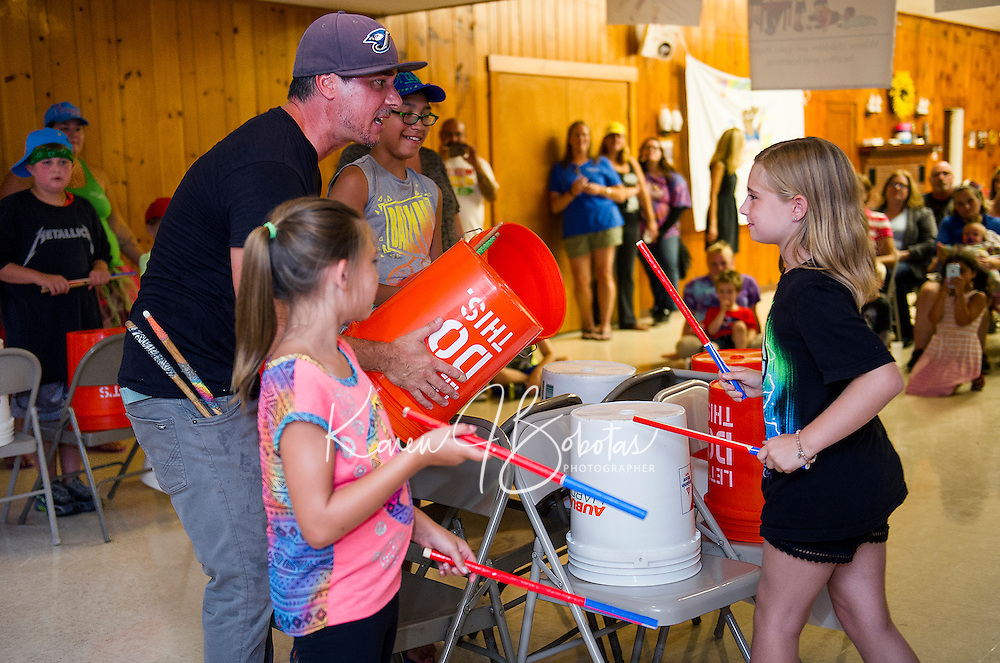 """Mr. Rich holds a drum while Zoe does a solo set during """"Youth Beatz"""" with Lakes Region Child Services at Leavitt Park Clubhouse on Tuesday evening.  (Karen Bobotas/for the Laconia Daily Sun)"""