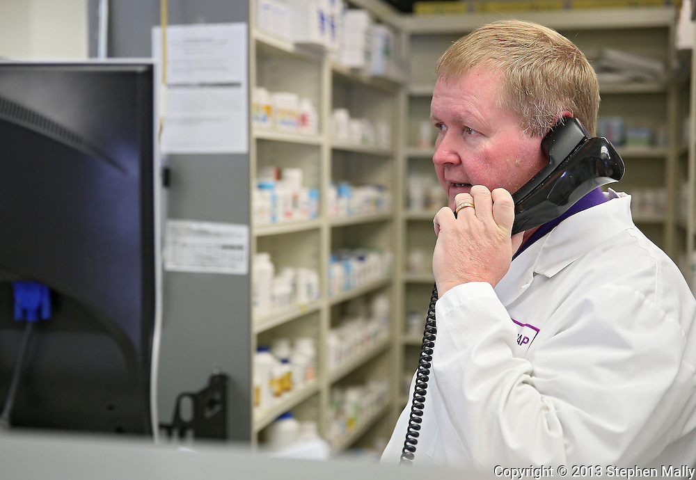 Pharmacist Gary Grabe talks on the phone at Medicap Pharmacy in Cedar Rapids on Tuesday, March 19, 2013.