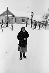 An old woman stands in front of enter of barrack where she lives in house for  released an old prisoners in village Blagoveshenka, Kemerovo region, Eastern Siberia, Russia, 08 December1999. Blagoveshensky house for an old former prisoners a special institution which is a part of a penitentiary system where live former prisoners which have age more then 55 years after released and haven't house or an apartment and relatives.