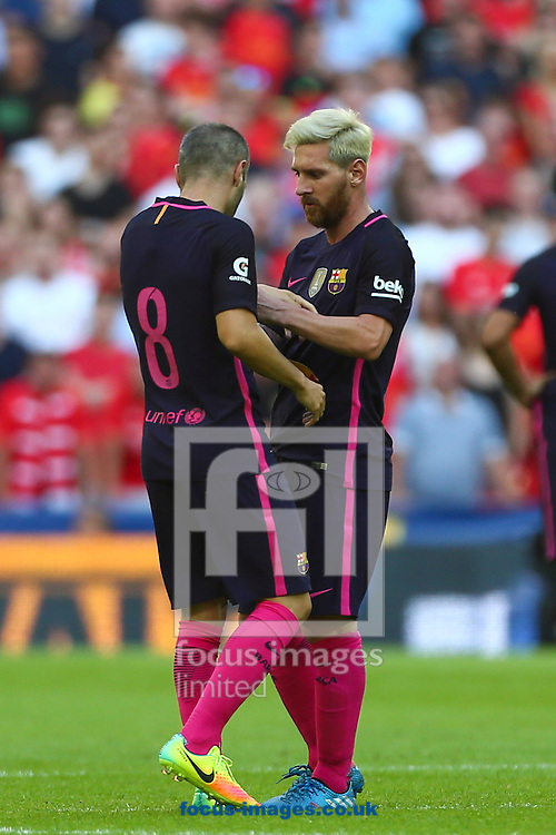 Lionel Messi of FC Barcelona hands Andres Iniesta of FC Barcelona the captains arm band during the International Champions Cup match at Wembley Arena, London<br /> Picture by Ryan Dinham/Focus Images Ltd +44 7900 436859<br /> 06/08/2016