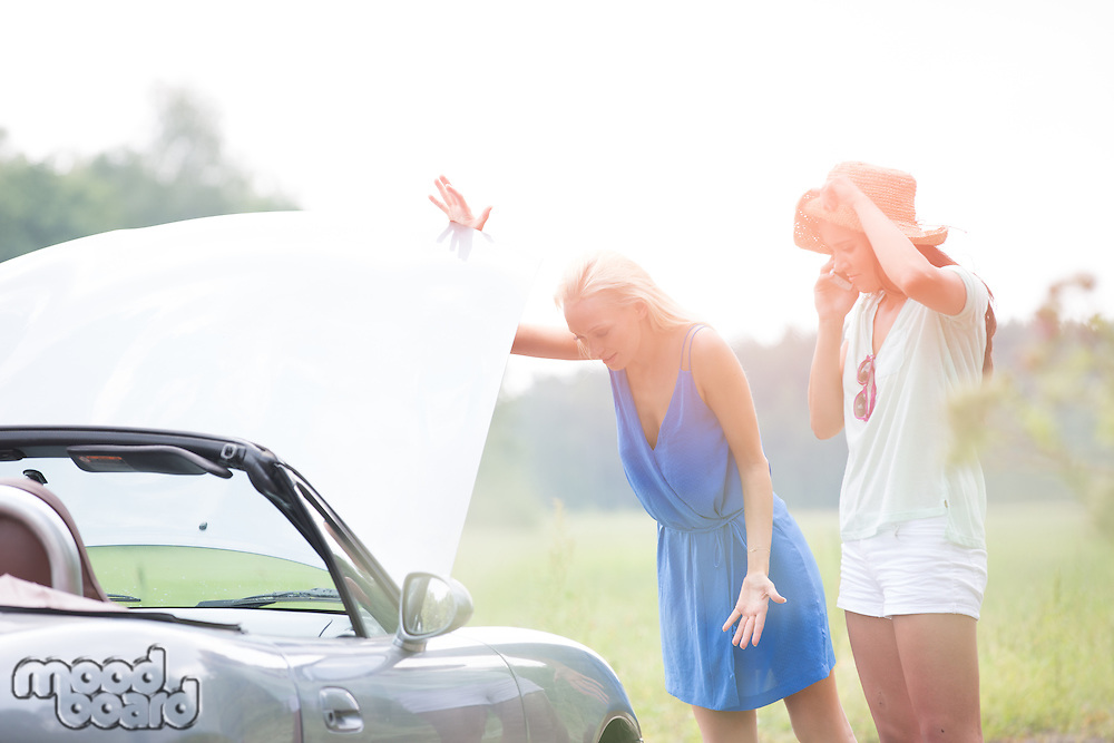 Worried female friends examining broken down car on sunny day