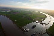 Nederland, Noord-Brabant, Gemeente Oss, 15-11-2010. Keent, Maas met Keentsche Uiterwaard bij hoogwater. De oorspronkelijk meander is in het kader van de Maasnormalisatie (kanalisatie) afgesneden. Dit naar aanleiding van de watersnood in het rivierengebied in 1926. Inmiddels wordt de oude rivierarm weer uitgegraven en aan één zijde met de Maas verbonden om bij hoogwater meer water uit de Maas te kunnen bergen..Meuse with Keent floodplain. The original meander has been cut during the Meuse Standardization (canalisation). This was done in response to the floods in 1926. Meanwhile, the old river arm is being excavated and one sided is reconnected to the river to create storage for water during high water..luchtfoto (toeslag), aerial photo (additional fee required).foto/photo Siebe Swart