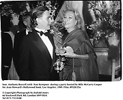 hon. Anthony Russell with  Nan Kempner  during a party hosted by Billy McCarty-Cooper for Jean Howard's Hollywood book. Los Angeles. 1989. Film.89320/25a<br />
