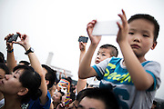 Chinese kids take pictures using their smartphones during the daily Chinese Army parade of the flag raising in Tiananmen Square in Beijing, China, July 19, 2014.<br /> <br /> Smartphones are an essential tool of Chinese ordinary life. Everywhere in China, people use them to take pictures to share online, to talk and chat, to play videogames, to get access to the mainstream information, to get connected one each other. In the country where the main global social media are forbidden - Facebook, Twitter and Youtube are not available  -, local social networks such as WeChat have a wide spread all over the citizens. The effect is an ordinary and apparently compulsive way to get easy access to digital technology and modern way of communication. <br /> A life through the display. Yes, We Chat.<br /> <br /> © Giorgio Perottino