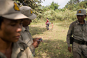 A mother and children walk down to the river past a group of forest rangers. The forest rangers are employed by the Ministry of Environment but sponsored by Flora and Fauna International who pays them 75% of their salary and provides training and accommodation. They undertake regular patrols in to the Samkos Wildlife Sancturary which is part of the Cardamom Mountains Nature Reserve looking for illegal activites such as logging, poaching, land encroachment and the production of the illegal substance sassafras oil. The Cardamom Mountains and surrounding forests is the largest and most pristine area of intact forest in SE Asia. Covering an area of 2.5 million acres it became one of the last strong holds of a retreating Khmer Rouge. Their presence helped preserve the forest as no-one dared to venture inside. But with the Khmer Rouge gone, it faces new dangers from poachers, loggers and illegal drug factories. In charge of protecting this vast forest are a handful of rangers who's job it is to track down and arrest those who are helping to destroy this delicate habitat.