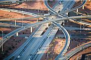 "Interchange (road) [From Wikipedia, the free encyclopedia] High-capacity freeway interchange in Los Angeles, California.In the field of road transport, an interchange is a road junction that typically utilizes grade separation, and one or more ramps, to permit traffic on at least one road to pass through the junction without crossing any other traffic stream. It differs from an intersection, at which roads cross at grade. Interchanges are almost always used when at least one of the roads is a freeway, though they may occasionally be used at junctions between two surface streets.A stack is an interchange in which left turns are handled by semi-directional flyover ramps. In order to go left, vehicles first turn slightly right (on a 'right-turn' ramp), then go left on a ramp which goes over (or under) both freeways and connects to the 'right-turn' ramp in the opposite quadrant of the interchange. A stack interchange, then, has two pairs of left-turning ramps, which can be ""stacked"" in various configurations above or below the two through routes. Stacks do not suffer from the problem of weaving associated with cloverleafs, but require massive construction works. A basic stack involves roads on four levels, but in stacks including ramps for direct movement between high occupancy vehicle lanes, even more levels of stack can be needed; the interchange between Interstate 105 and Interstate 110 in Los Angeles County, California, is a five-level stack. This is not only expensive, but also unsightly, leading to considerable NIMBY opposition. Large stacks with multiple levels are sometimes referred to as Mixmasters in the United States."