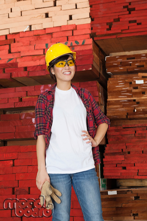 Asian female industrial worker looking away with stacked wooden planks in background