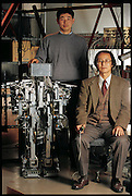 "Posing for a portrait at the Osaka  (Japan) University Department of Computer-Controlled Mechanical Systems, Junji Furusho (seated) and research associate Masamichi Sakaguchi show off Strut, their child-sized humanoid robot. At the time, the robot, a work in progress, could not walk at all?it could only stand. (It walked sometime later.) But simply getting the robot to stand properly was a major accomplishment. Like a human being, Strut has such complex, interreacting mechanical ""musculature"" that considerable processing power is needed simply to keep it erect. Japan. From the book Robo sapiens: Evolution of a New Species, page 49."