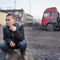 China, Shanxi Province, Datong, Portrait of young man smoking cigarettes beside coal trucks outside coal-fired Datong No. 2 Power Station