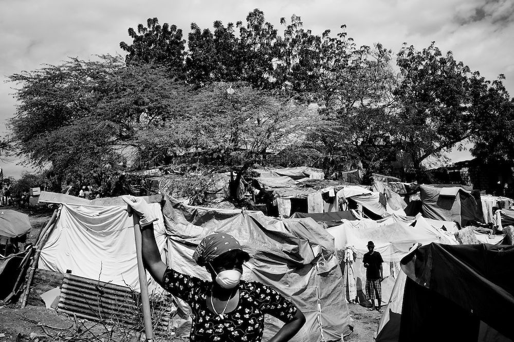 Residents of a camp for those displaced by the recent earthquake shovel trash in Petionville, outside Port-au-Prince, Haiti.