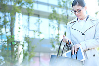 Businesswoman putting digital tablet in purse outdoors