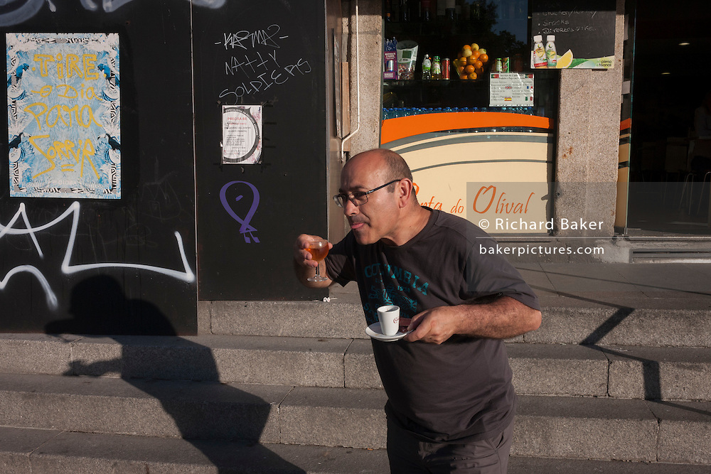 A man pretends to sip someone's wine while returning from a cafe in Porto, Portugal.