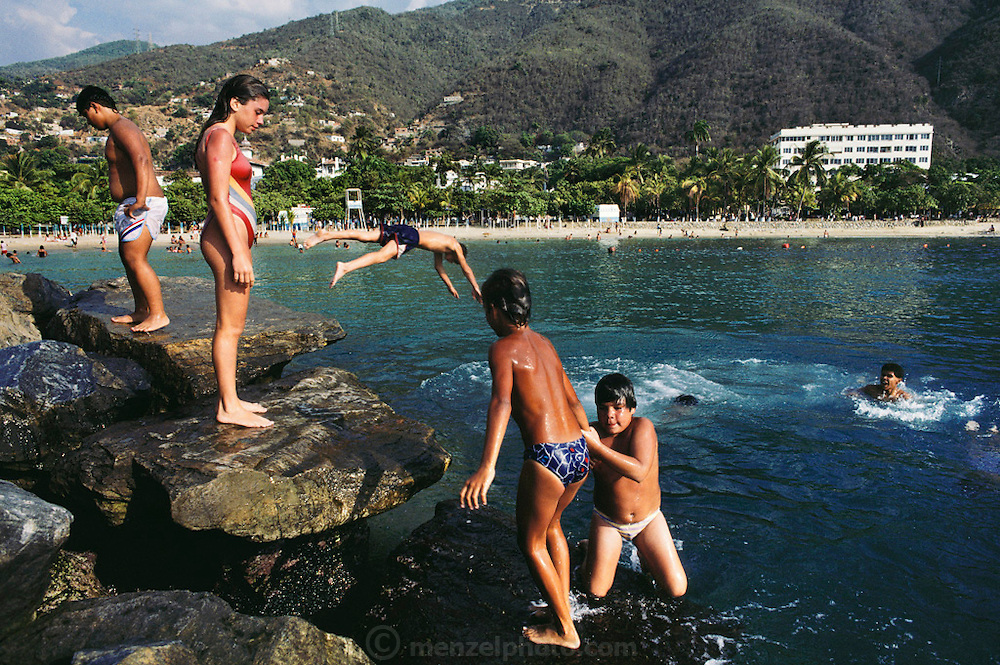 Young people swimming and diving off the rocks into the sea at Macuto, Venezuela.