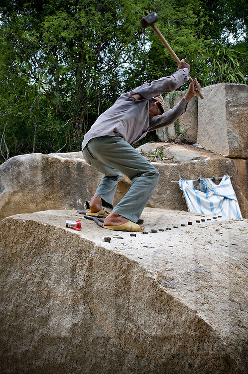 A worker is trying his best to punch a huge stone. He lifts a hammer high then hits on chisels already set into stone to make it splited out. Khanh Hoa province, Vietnam, Asia.