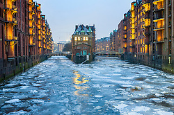 View of historic red brick warehouses with frozen canals in winter  at Speicherstadt beside canals in Hamburg Germany