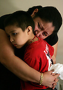 Clara Pineda hugs her five-year-old son Juan, who's father, Serjio, was murdered last night while returning from an errand.
