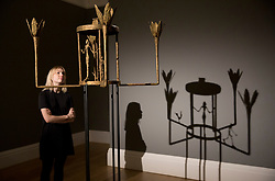 """© Licensed to London News Pictures. 22/02/2018. LONDON, UK. A member of staff looks at """"Lustre avec femme, homme et oiseau"""" (1952) by Alberto Giacometti Picasso with an estimate of £6,000,000 — 8,000,000, on display at Sotheby's photo call for highlights from their forthcoming sales of Impressionist, Modern, Surrealist and Contemporary Art. Photo credit: ISABEL INFANTES/LNP"""