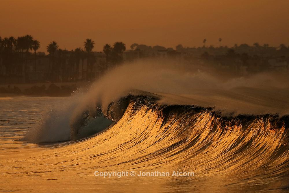 A wave breaks at sunrise in Venice Beach, California