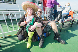 © Licensed to London News Pictures. 11/06/2015. East Cowes, UK.  Festival goers wearing wellies and mexican sombreros travelling to Isle of Wight Festival 2015 on the Southampton-East Cowes ferry early on thursday morning. surrounded by their bags and tents.This years festival include headline artists the Prodigy, Blur and Fleetwood Mac.  Photo credit : Richard Isaac/LNP