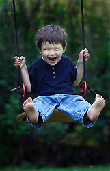 A happy smiling child on a swing. (Photo © Jock Fistick)