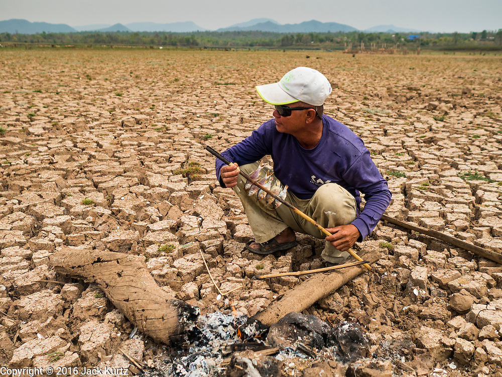 02 APRIL 2016 - NA SAK, LAMPANG, THAILAND:  A man cooks fish he trapped in Mae Chang Reservoir in what used to be Sobjant village. The flats he's cooking should be under two meters of water at this time of year. He trapped the fish in a puddle about 500 meters from his cooking fire. The village of Sobjant in Na Sak district in Lampang province was submerged when the Mae Chang Reservoir was created in the 1980s. The village was relocated to higher ground a few kilometers from its original site. The drought gripping Thailand drained the reservoir and the foundations of the Buddhist temple in the original village became visible early in 2016. Thai families come down to the original village to pray in the ruins of the temple and look at what's left of the village.     PHOTO BY JACK KURTZ