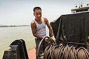 24 APRIL 2014 - CHIANG SAEN, CHIANG RAI, THAILAND: A crewman on a Chinese cargo boat on the Mekong River pulls up the anchor as the boat, carrying a cargo of cars, Red Bull energy drink and passengers heads up the Mekong bound for Kunming in China. Chinese businesses play an increasingly important role in the Chiang Rai economy. Consumer goods made in China are shipped to Thailand while agricultural products made in Thailand are shipped to China. Large Chinese cargo boats ply the Mekong River as far south as Chiang Saen in the dry season and Chiang Khong when river levels go up in the rainy season.    PHOTO BY JACK KURTZ