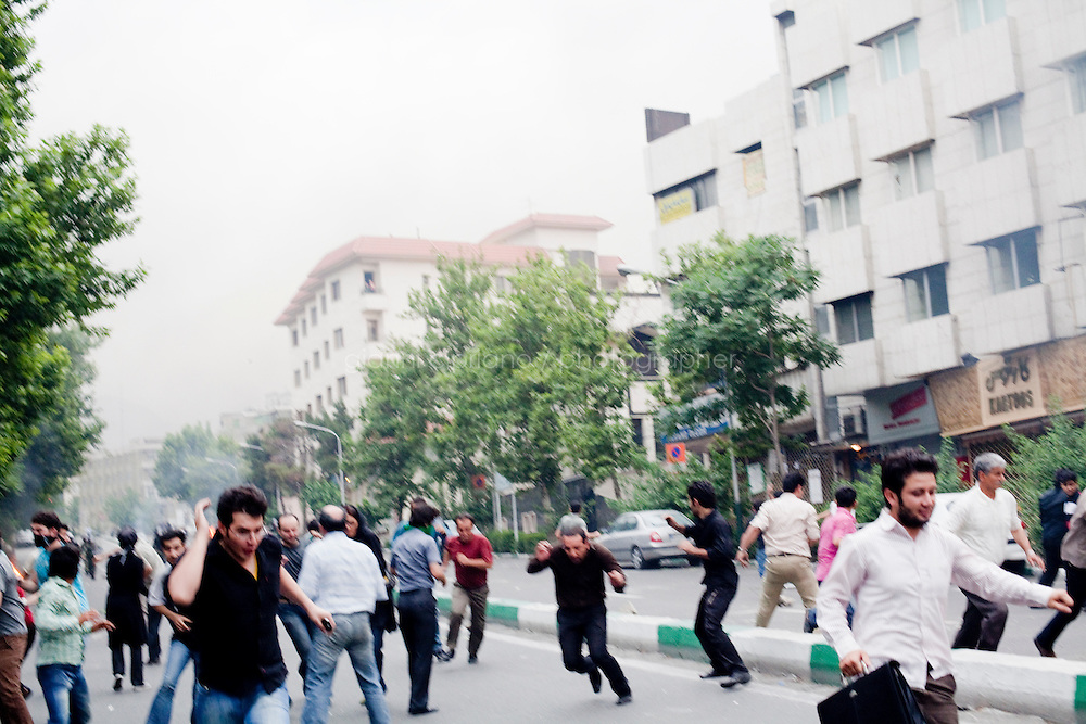 13 June, 2009. Tehran, Iran. Supporters of reformist candidate Mir Hossein Moussavi run away from the police firing tear gas. Police clamped down on supporters of the opposition candidate, Mir Hussein Moussavi, who said the election was stolen by President Ahmadinejad. Conservative reformist candidate Mir Hossein Mousavi ran against the ultra-conservative current President of Iran Mahmoud Ahmadinejad.<br /> &copy;2009 Gianni Cipriano<br /> cell. +1 646 465 2168 (USA)<br /> cell. +39 328 567 7923<br /> gianni@giannicipriano.com<br /> www.giannicipriano.com