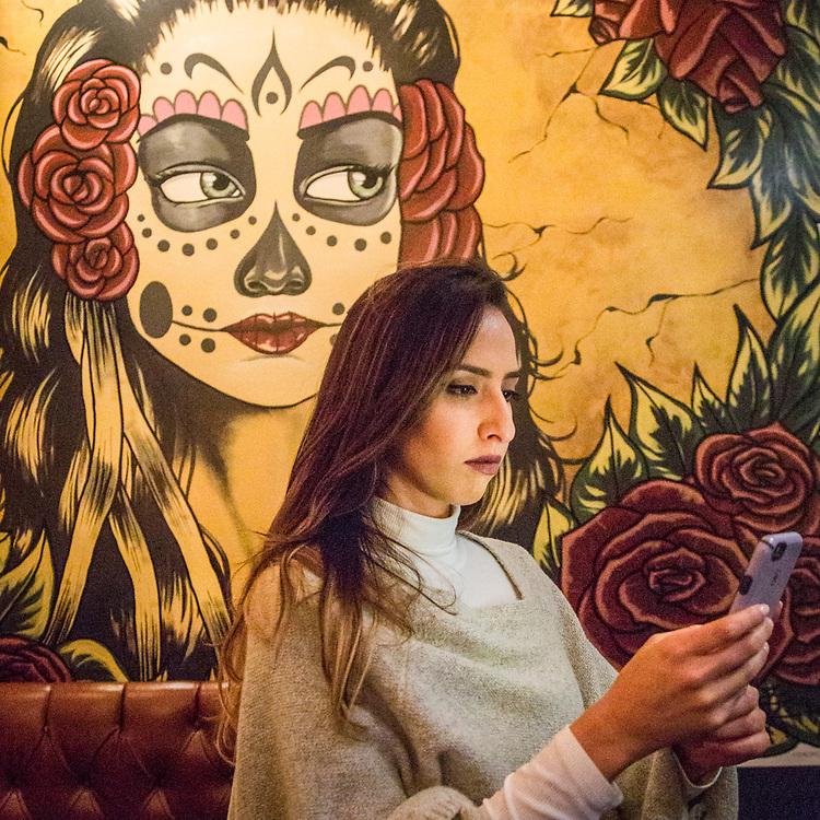 Reena Rai checks messages at Papito Hays in San Francisco.