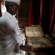 A priest reads from an ancient holy book inside the Bet Gabriel-Rafael church in Lalibela. Lalibela's churches are in carved out of red volcanic stone. Bet Gebriel-Rafael has a plunging facade. Christianity came to Ethiopia in the 4th century and the Ethiopian Orthodox Church has retained its own unique traditions.