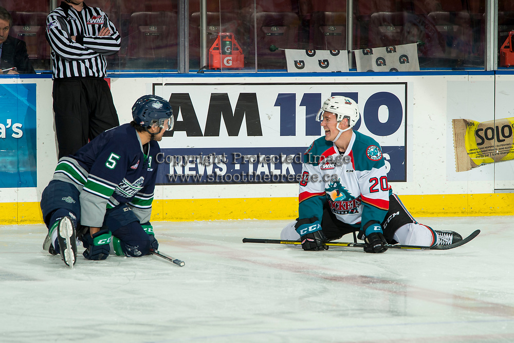 KELOWNA, CANADA - JANUARY 30: Jarret Tyszka #5 of the Seattle Thunderbirds and Conner Bruggen-Cate #20 of the Kelowna Rockets share a laugh while stretching at centre ice during warm up on January 30, 2019 at Prospera Place in Kelowna, British Columbia, Canada.  (Photo by Marissa Baecker/Shoot the Breeze)