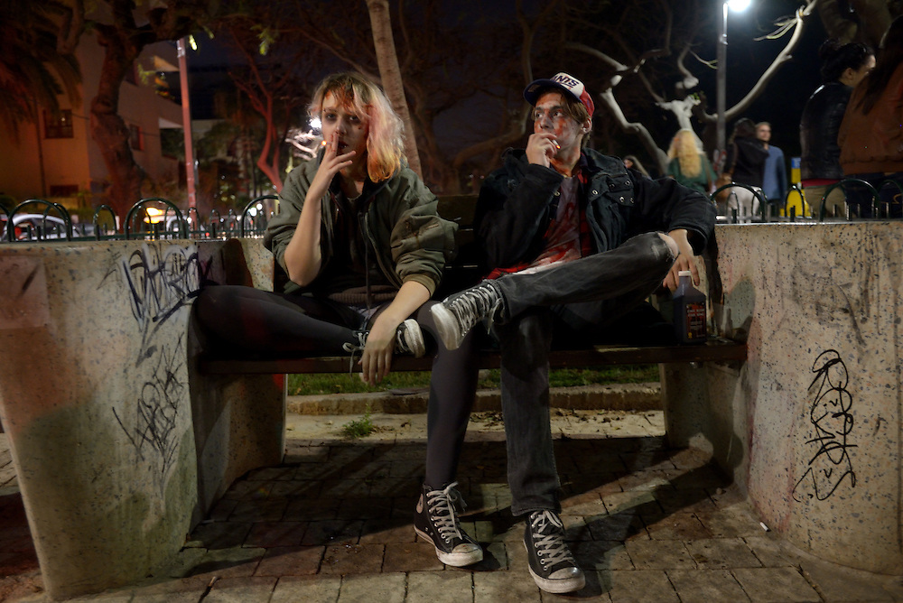 TEL AVIV, ISRAEL - MAR 15, 2014: An Israeli couple wearing zombie make-up are sitting on a bench and smoking cigarettes while participating the Zombie Walk during the Purim festival in Tel Aviv. The Zombie Walk is held in tel Aviv during Purim Holiday in which Jewish traditionaly wear costumes. Photo by Gili Yaari
