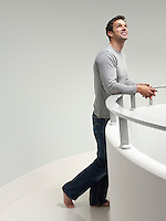 Young man leaning on railing indoors looking up