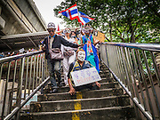 "02 JUNE 2013 - BANGKOK, THAILAND: A legless man leads a protest march down a flight of stairs through the Bangkok skywalk system. About 300 people wearing the Guy Fawkes mask popularized by the movie ""V for Vendetta"" and Anonymous, the hackers' group, marched through central Bangkok Sunday demanding the resignation of Prime Minister Yingluck Shinawatra. They claim that Yingluck is acting as a puppet for her brother, former Prime Minister Thaksin Shinawatra, who was deposed by a military coup in 2006 and now lives in exile in Dubai.      PHOTO BY JACK KURTZ"