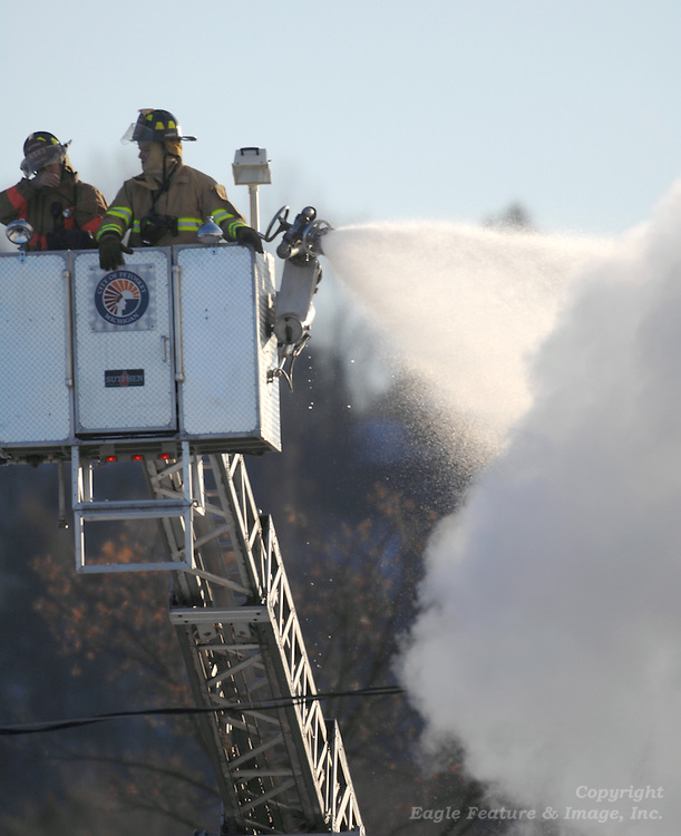 Fire fighters from the Petoskey fire department's ladder truck (upper left) pour water onto the roof of long time Petoskey florist business Alfie's Attic (right) and the neighboring Side Door Saloon both located on U.S. 31 in Petoskey.  Fire fighters from at least five northern Michigan responded to the blaze.